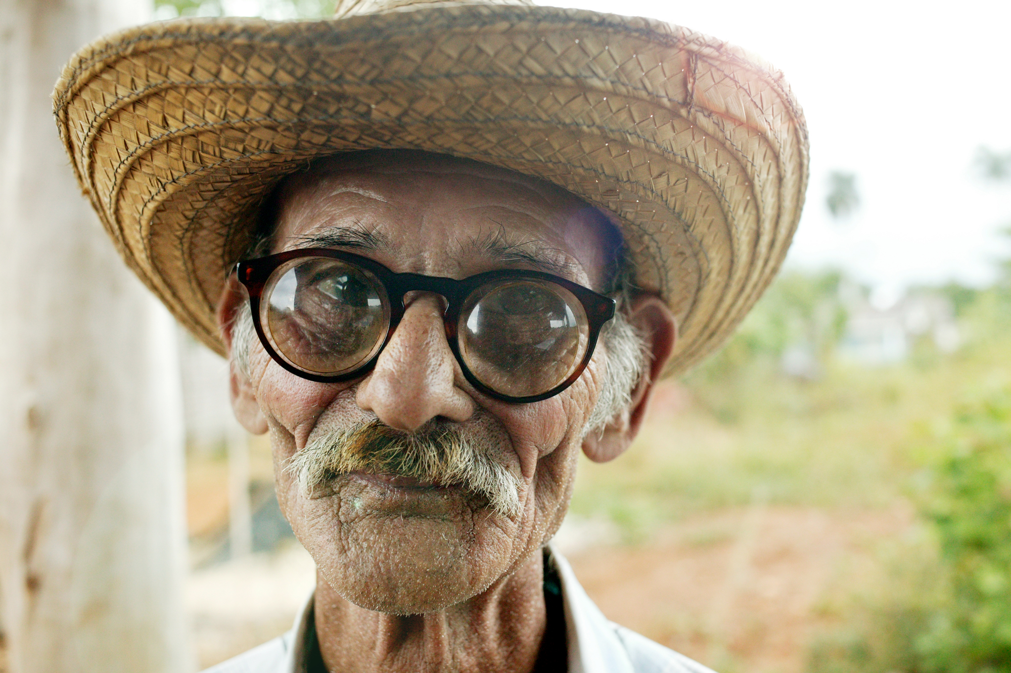 portrait of cuban farmer with thick glasses and straw hat