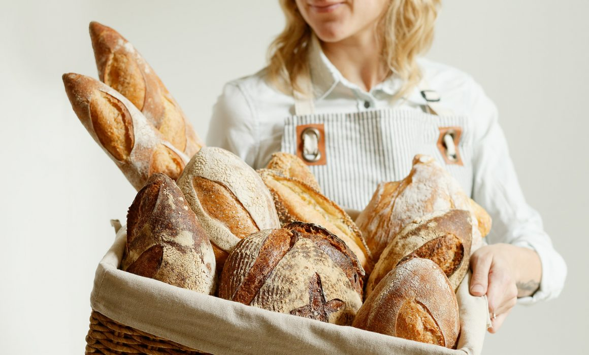 woman in apron holding a big basket of artisan bread